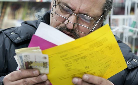 Мужчина заполняет квитанции на оплату коммунальных услуг